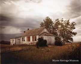 Abandoned white schoolhouse under dark skies